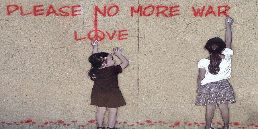 niñas pidiendo paz escribiendo grafitti en muro